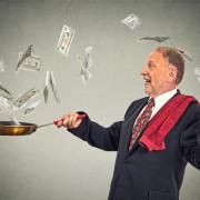 Happy senior elderly business man juggling money dollar bills banknotes isolated on grey wall background
