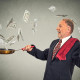 Happy senior elderly business man juggling money dollar bills banknotes isolated on grey wall background